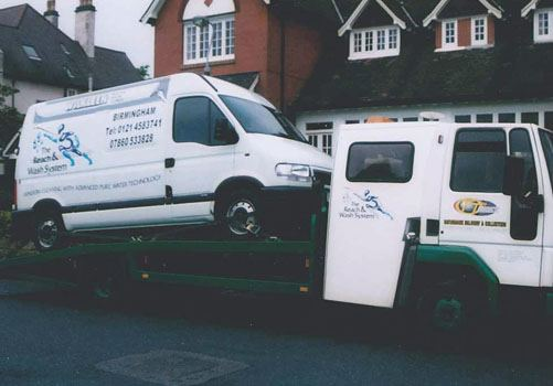 Reach & Wash company van being lifted on the back of a truck