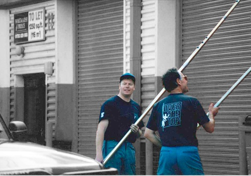 Two people cleaning with pure water using waterfed poles